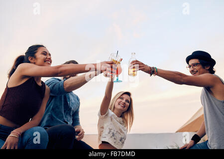 Happy friends celebrating the success with a toast at rooftop party. Young men and women toasting cocktails at party. - Stock Photo