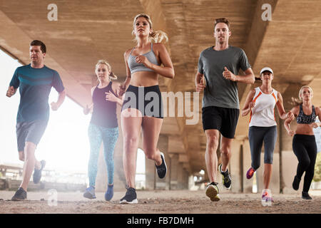 Determined  group of young people running together in city. Low angle shot of running club members training together - Stock Photo
