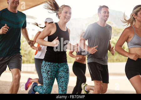 Group of happy young friends running together. Running club members exercising. - Stock Photo