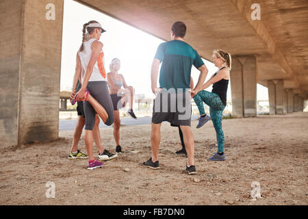 Group of healthy people stretching under a city bridge. Young men and woman taking a break from outdoor training. - Stock Photo