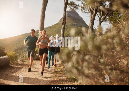 Group of young adults training and running together through trails on the hillside outdoors in nature. Fit young - Stock Photo