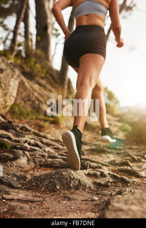 Woman running on rocky trails on the hillside. Rear view image of female runner training outdoors. - Stock Photo
