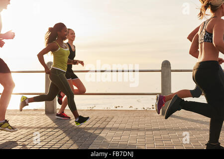 Young woman running with friends on seaside promenade at the sunset. Fit young people doing running workout outdoors - Stock Photo