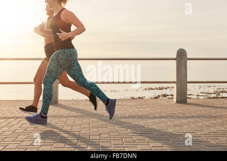 Cropped shot of two young women running along a seaside promenade. Healthy young runners working out together on - Stock Photo