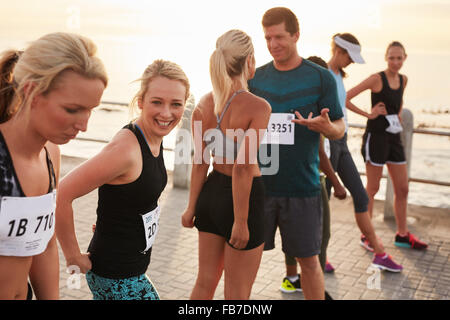 Group of happy young athletes standing on starting line and talking before start of the race. Running club group - Stock Photo