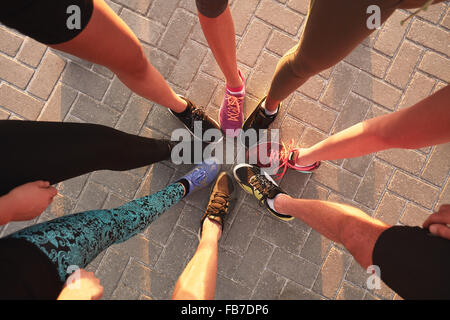 Legs of athletes wearing sports shoes in a circle. Top view of runners standing together. - Stock Photo