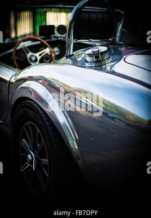 aluminum body convertible AC Cobra rear drivers side view showing fuel cap and steering wheel - Stock Photo