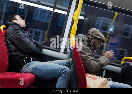 Two men listening to music on their phones on London bus - Stock Photo