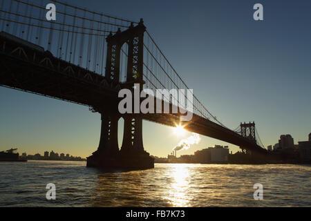 The sun rises under the Manhattan Bridge spanning the East River joining Manhattan to DUMBO, Brooklyn - Stock Photo