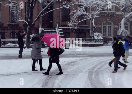 Unknown people, including a woman with a red umbrella, walk along snow covered Joralemon Street in Brooklyn Heights - Stock Photo