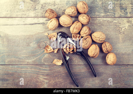 Vintage stylized walnuts and nutcracker on wooden background, space for text. - Stock Photo