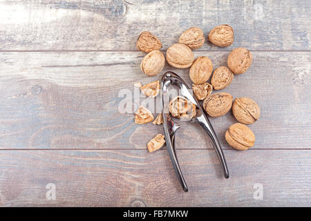 Walnuts and nutcracker on wooden background, space for text. - Stock Photo