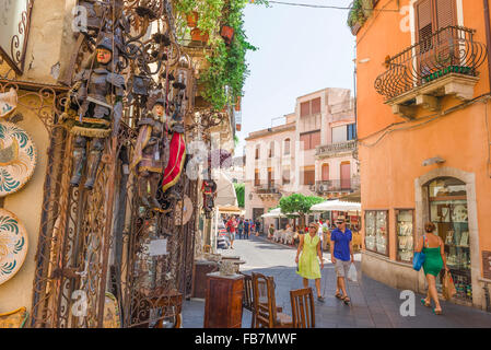 Taormina shopping Sicily, view of a middle-aged tourist couple looking at an elaborate display outside an antiques - Stock Photo