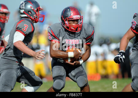 After accepting a hand off, a running back surveys looking for an opening in the defense during a high school football - Stock Photo