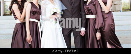 Handsome groom in suit hugging elegant bride with bridesmaids - Stock Photo