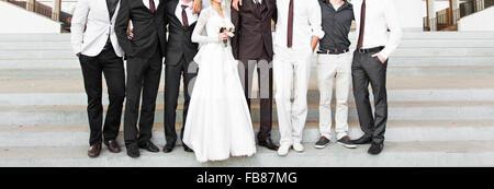 Handsome groom in suit hugging elegant bride and groomsmen - Stock Photo