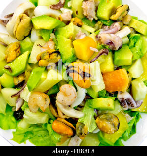 Salad from shrimps, octopus, mussels and calamari with avocado, lettuce, pineapple isolated on white background - Stock Photo