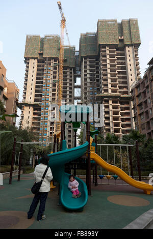 A toddler plays at the playground of a gated community while the complex of flats continues to expand with highrise - Stock Photo