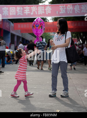 A mixed-race toddler and her Chinese mother at a trade fair in a city in China. - Stock Photo