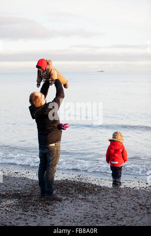 Denmark, Grenen, Father with daughters (6-11 months) ( 2-3) playing on beach - Stock Photo
