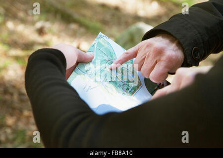 Sweden, Skane, Soderasen, Hand pointing at map in national park - Stock Photo