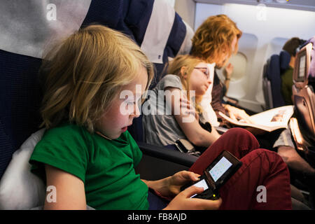 Sweden, Mother travelling by plane with children (6-7, 10-11) - Stock Photo