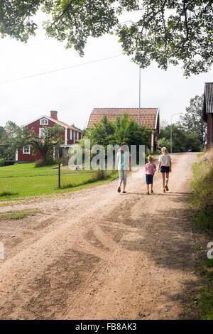 Sweden, Smaland, Vastervik, Hummelstad, Rear view of children (6-7, 10-11, 12-13) walking along village road - Stock Photo