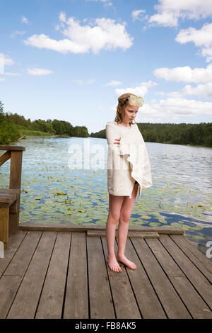 Sweden, Stockholm, Nacka, Sicklasjon, Lake Sickla, Girl (10-11) wrapped in towel standing on wooden jetty after - Stock Photo