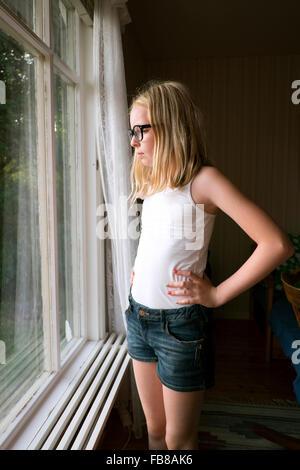 Sweden, Skane, Vejbystrand, Girl (10-11) looking though window - Stock Photo