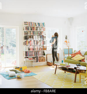 Sweden, Woman with her baby (12-17 months) in domestic room - Stock Photo