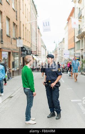 Sweden, Uppland, Stockholm, Drottninggatan, Policewoman talking with man on street - Stock Photo