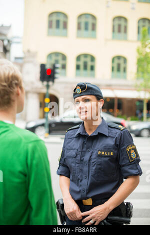 Sweden, Uppland, Stockholm, Policewoman talking with man on street - Stock Photo