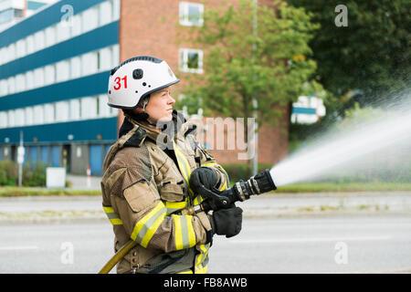 Sweden, Sodermanland, Sodertalje, Female firefighter using fire hose in street - Stock Photo