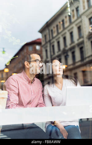 Sweden, Uppland, Stockholm, Man and woman sitting in cafe - Stock Photo