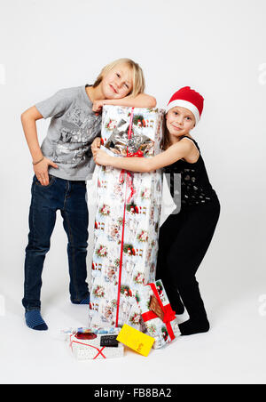 Pre-teen boy (10-11) and girl (8-9) posing with pile of Christmas presents - Stock Photo