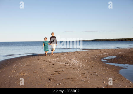 Sweden, Medelpad, Bergafjarden, Brother (10-11) with sister (6-7) walking along Baltic coast - Stock Photo