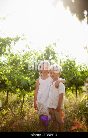 Italy, Tuscany, Portrait of sister (6-7) embracing younger brother (4-5) in orchard - Stock Photo