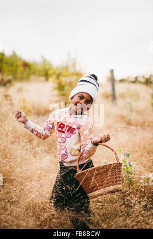 Sweden, Medelpad, Sundsvall, Juniskar, Portrait of smiling girl (6-7) holding basket - Stock Photo