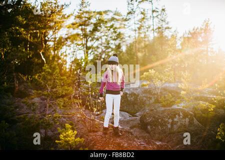 Sweden, Medelpad, Sundsvall, Juniskar, Portrait of girl (10-11) standing in forest on sunny day - Stock Photo