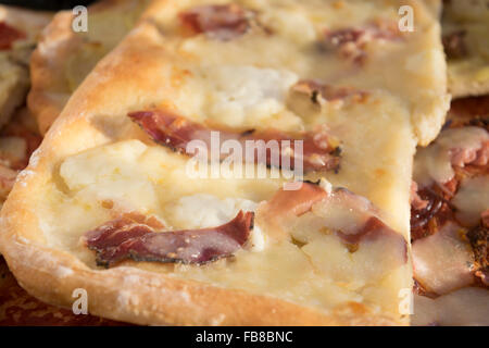 variety of homemade pizza cut in small pieces - Stock Photo