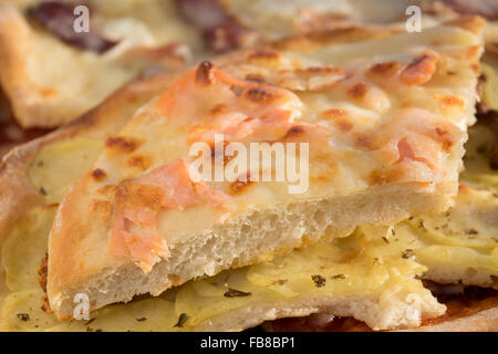 homemade pizza with smoked salmon and mozzarella cut in small pieces - Stock Photo