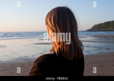 Spain, The Basque Country, Gipuzkoa, San Sebastian, Woman standing on beach and looking at Bay of Biscay at sunset - Stock Photo