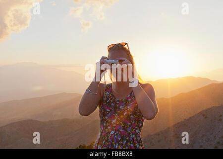 USA, California, Joshua Tree National Park, Female tourist photographing landscape at sunset - Stock Photo