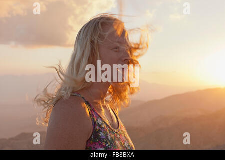 USA, California, Joshua Tree National Park, Female tourist relaxing in mountain landscape at sunset - Stock Photo