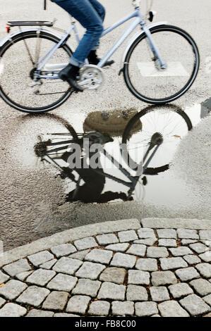 Sweden, Vastra Gotaland, Gothenburg, Women cycling on wet street - Stock Photo