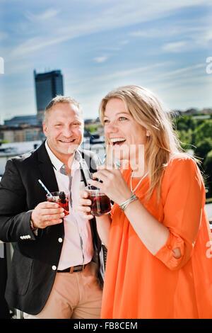Sweden, Uppland, Stockholm, Portrait of couple drinking cocktails - Stock Photo