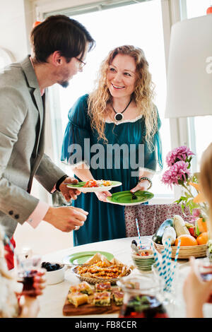 Sweden, Friends talking during party - Stock Photo