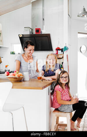 Sweden, Mother and daughters (6-7, 8-9) smiling in kitchen - Stock Photo