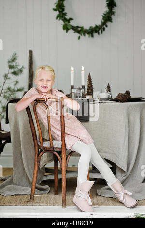Sweden, Young girl (6-7) sitting on chair in living room during Christmas - Stock Photo