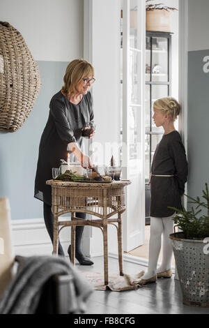 Sweden, Grandmother with granddaughter (6-7) standing in living room during Christmas - Stock Photo